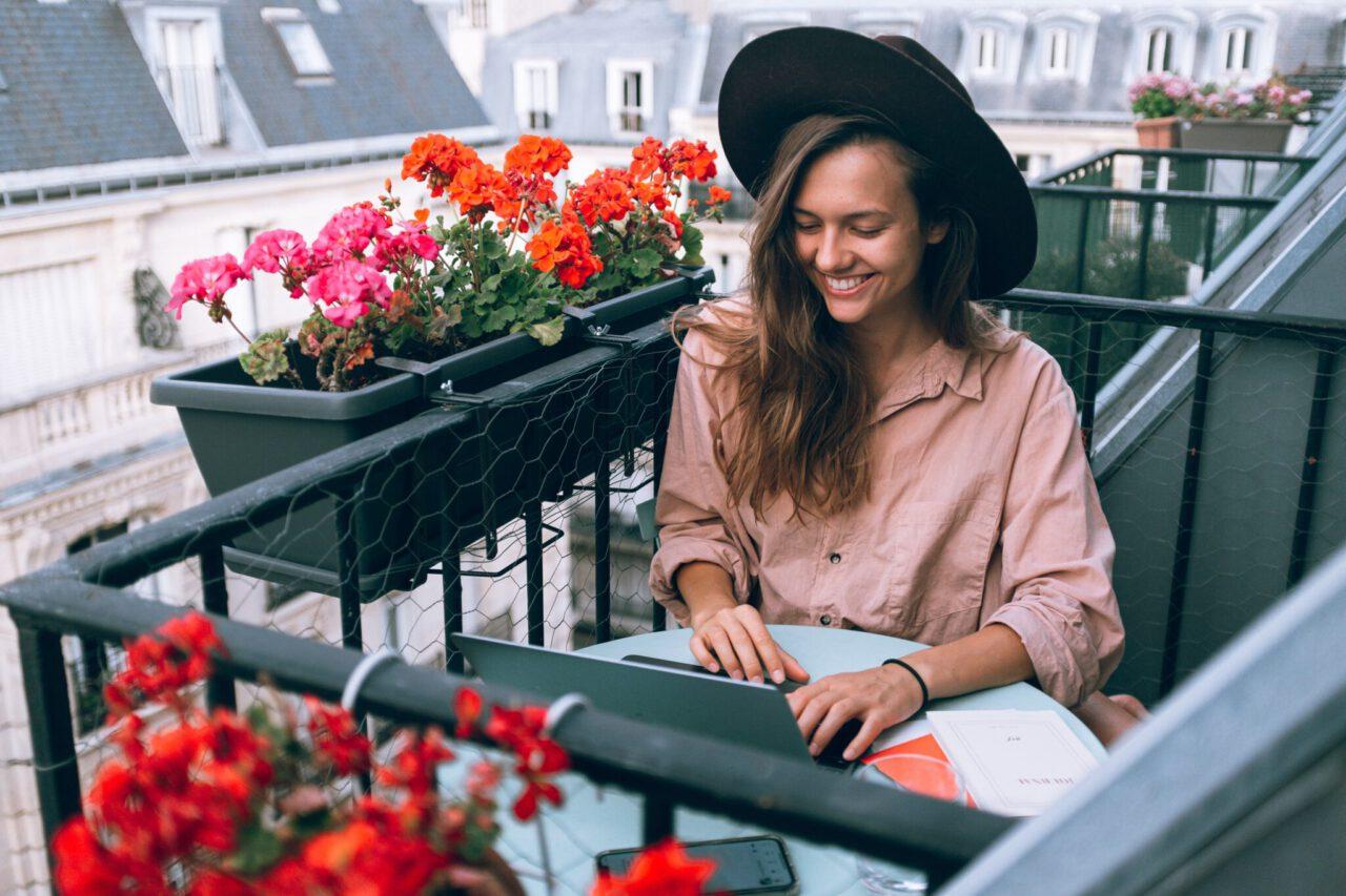 Vrouw op balkon met laptop